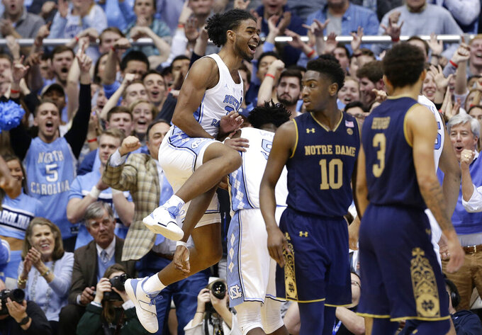 North Carolina's Coby White jumps while celebrating with Nassir Little while Notre Dame's TJ Gibbs (10) and Prentiss Hubb (3) walk away following a play during the second half of an NCAA college basketball game in Chapel Hill, N.C., Tuesday, Jan. 15, 2019. North Carolina won 75-69. (AP Photo/Gerry Broome)