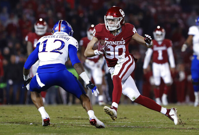 Oklahoma tight end Grant Calcaterra (80) runs as Kansas safety Jeremiah McCullough (12) looks to block during the second half of an NCAA college football game in Norman, Okla., Saturday, Nov. 17, 2018. Oklahoma won 55-40. (AP Photo/Alonzo Adams)