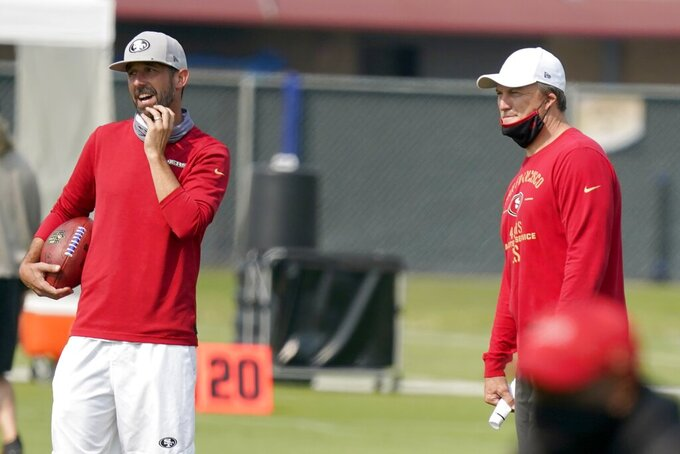 San Francisco 49ers general manager John Lynch, right, and head coach Kyle Shanahan watch players warm up during NFL football practice at the team's training facility in Santa Clara, Calif., Sunday, Aug. 23, 2020.  (Tony Avelar/San Francisco Chronicle via AP, Pool)