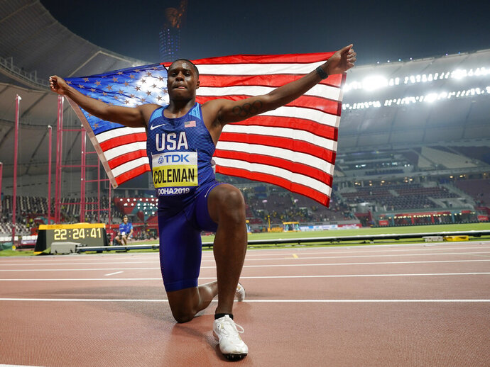 FILE - In this  Sept. 28, 2019, file photo, Christian Coleman, of the United States, celebrates winning the gold medal in the men's 100 meter final race at the World Athletics Championships in Doha, Qatar. Men's 100-meter world champion Christian Coleman was banned for two years on Tuesday, Oct. 27, 2020, for missing three doping control tests. Track and field's Athletics Integrity Unit said Coleman will be banned until May 2022, forcing him to miss the Tokyo Olympics next year. (AP Photo/David J. Phillip)