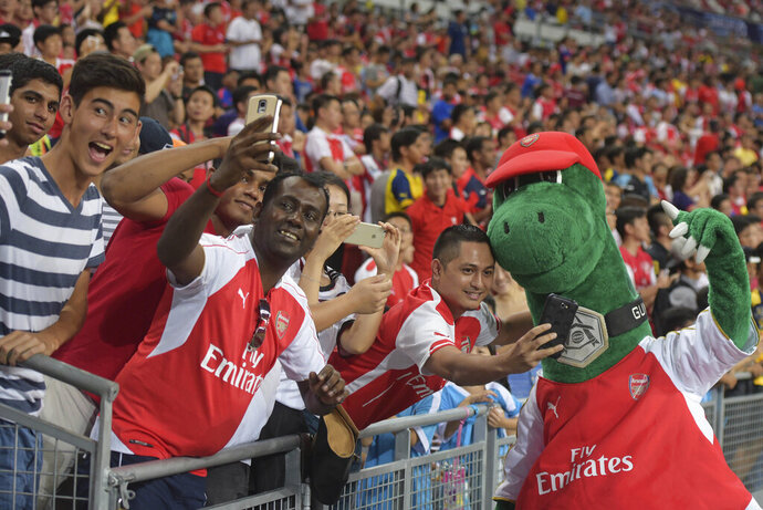 FILE - In this Saturday, July 18, 2015 file photo, fans pose for pictures with Arsenal's mascot Gunnersaurus ahead of their team's soccer match against Everton for the Barclays Asia Trophy in Singapore. Out-of-favor Arsenal playmaker Mesut Ozil wants to save Gunnersaurus from extinction. Ozil expressed sadness Tuesday Oct. 6, 2020, after discovering that Jerry Quy — the man who fills the Arsenal dinosaur mascot outcut — had been made redundant by the London club after 27 years. (AP Photo/Joseph Nair, File)