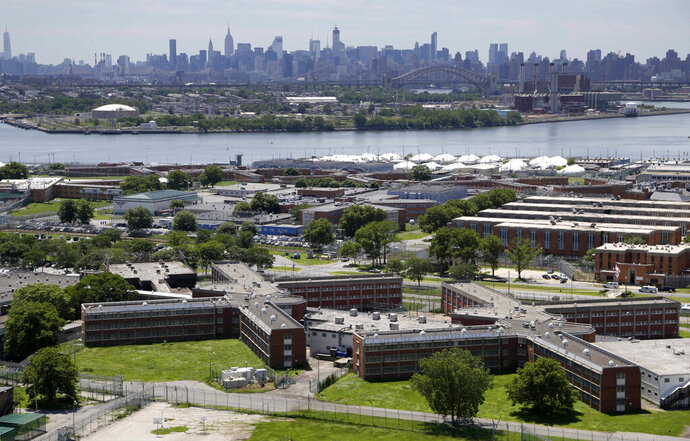 FILE - This June 20, 2014 file photo shows the Rikers Island jail complex in New York with the Manhattan skyline in the background. New York City lawmakers are considering a plan to close the notorious Rikers Island jail complex and replace it with four smaller jails. The City Council is set to vote Thursday, Oct. 17, 2019 on a plan to build the jails that would replace Rikers. (AP Photo/Seth Wenig, File)