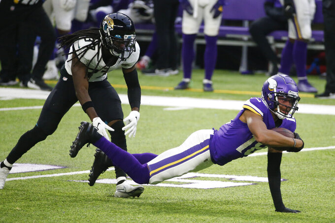 Minnesota Vikings wide receiver Justin Jefferson, right, dives for extra yardage ahead of Jacksonville Jaguars cornerback Tre Herndon, left, during the second half of an NFL football game, Sunday, Dec. 6, 2020, in Minneapolis. (AP Photo/Bruce Kluckhohn)