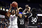 FILE - In this March 9, 2020, file photo, Connecticut's Christyn Williams (13) shoots over Cincinnati's IImar'I Thomas (23) and Florence Sifa (30) during the first half of an NCAA college basketball game in the American Athletic Conference tournament finals at Mohegan Sun Arena in Uncasville, Conn. UConn, are back home in the Big East sitting in a familiar spot — atop the preseason poll. The Huskies, who returned to the conference after seven years in the American, were the unanimous choice to win the league the Big East announced Thursday, Oct. 29, 2020. (AP Photo/Jessica Hill, File)