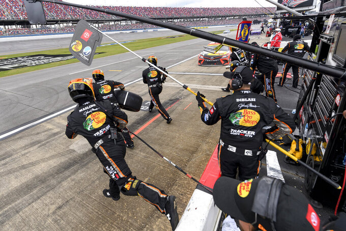 Crew members leap into action as Martin Truex Jr. nears his pit area during a NASCAR Cup series auto race Monday, Oct. 4, 2021, in Talladega, Ala. (AP Photo/John Amis)
