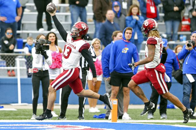 Oklahoma quarterback Caleb Williams (13) holds the ball in the air while scoring a touchdown against Kansas during an NCAA college football game, Saturday, Oct. 23, 2021, in Lawrence, Kan. (Ian Maule/Tulsa World via AP)
