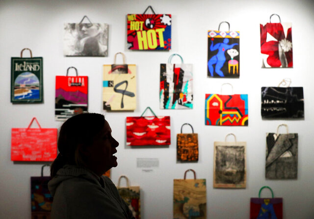 In this Tuesday, Dec. 17, 2019, photo, Jodi Kearns, director at the Institute for Human Science and Culture, takes a look at the small display of Bloomingdale's shopping bags from the Lee L. Forman Collection of Bags, in Akron, Ohio. The big batch of bags donated to UA includes shopping bags autographed by artists Andy Warhol and Roy Lichtenstein, and at least one bag from every presidential election since 1948. (Jeff Lange/Akron Beacon Journal via AP)