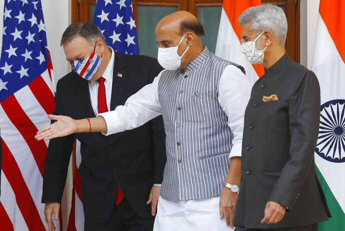 Indian Defence Minister Rajnath Singh, center, gestures towards U.S. Secretary of State Mike Pompeo, left, with Indian Foreign Minister Subrahmanyam Jaishankar, right, standing beside him, ahead of their meeting at Hyderabad House in New Delhi, India, Tuesday, Oct. 27, 2020. In talks on Tuesday with their Indian counterparts, Pompeo and Esper are to sign an agreement expanding military satellite information sharing and highlight strategic cooperation between Washington and New Delhi with an eye toward countering China. (Adnan Abidi/Pool via AP)