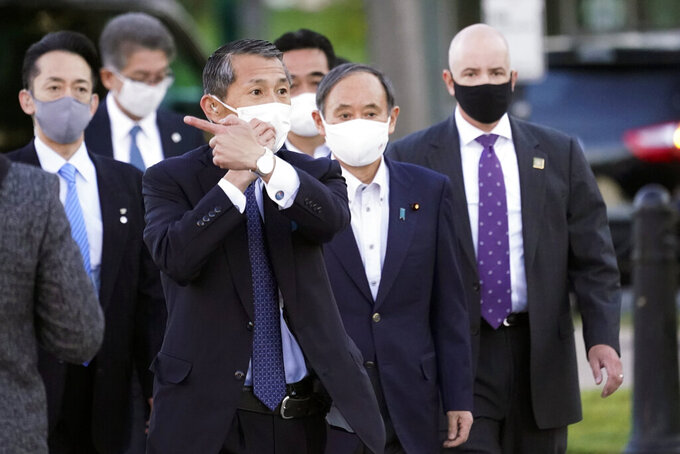 Japanese Prime Minister Yoshihide Suga, second from right, walks Saturday, April 17, 2021, in Washington. (AP Photo/Alex Brandon)