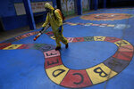 A government employee disinfects a public school as a measure against the spread of the new coronavirus, in the Taguatinga neighborhood of Brasilia, Brazil, Tuesday, July 28, 2020. The local government has began preparing for the safe reopening of schools in mid-August, as restrictions related to the COVID-19 lockdown are eased. (AP Photo/Eraldo Peres)