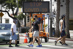 FILE - In this July 12, 2020, file photo, pedestrians wear masks as they cross a street amid the coronavirus pandemic in Santa Monica, Calif. The torrid coronavirus summer across the Sun Belt is easing after two disastrous months that brought more than 35,000 deaths. (AP Photo/Marcio Jose Sanchez, File)