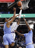 Northwestern forward Vic Law, center, shoots against Columbia forward Patrick Tape, left, and guard/forward Rodney Hunter during the second half of an NCAA college basketball game Sunday, Dec. 30, 2018, in Evanston, Ill. Northwestern won 75-54. (AP Photo/Nam Y. Huh)
