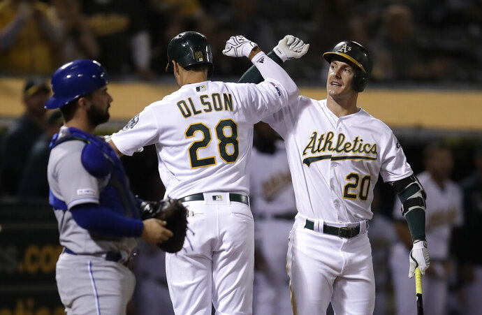 Oakland Athletics' Matt Olson (28) celebrates with Mark Canha, right, after hitting a home run off Kansas City Royals' Jorge Lopez during the seventh inning of a baseball game Tuesday, Sept. 17, 2019, in Oakland, Calif. (AP Photo/Ben Margot)