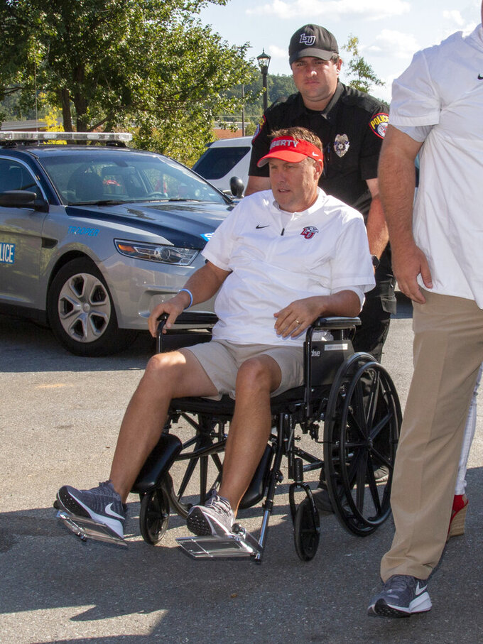 Liberty head football coach Hugh Freeze arrives to coach from a wheelchair in the coaches' box against Syracuse in an NCAA college football game in Lynchburg, Va., Saturday, Aug. 31, 2019. (AP Photo/Matt Bell)