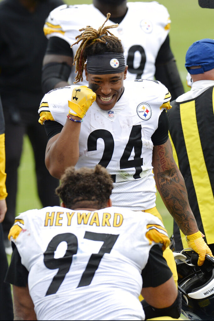 Pittsburgh Steelers running back Benny Snell (24) and end Cameron Heyward (97) celebrate after an NFL football game against the Tennessee Titans Sunday, Oct. 25, 2020, in Nashville, Tenn. The Steelers won 27-24. (AP Photo/Mark Zaleski)