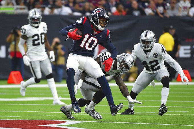 Houston Texans wide receiver DeAndre Hopkins (10) is hit by Oakland Raiders outside linebacker Tahir Whitehead (59) after a catch during the second half of an NFL football game Sunday, Oct. 27, 2019, in Houston. (AP Photo/Eric Christian Smith)