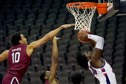 Liberty's Micaiah Abii, right, gets past South Carolina's Justin Minaya (10) to put up a basket during the first half of an NCAA college basketball game Saturday, Nov. 28, 2020, at the T-Mobile Center in Kansas City, Mo. (AP Photo/Charlie Riedel)