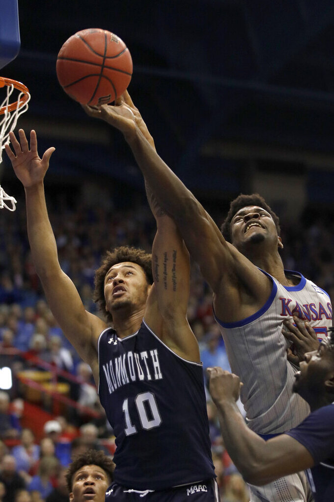Kansas center Udoka Azubuike, top right, rebounds, against Monmouth forward Jarvis Vaughan (10) during the first half of an NCAA college basketball game in Lawrence, Kan., Friday, Nov. 15, 2019. (AP Photo/Orlin Wagner)