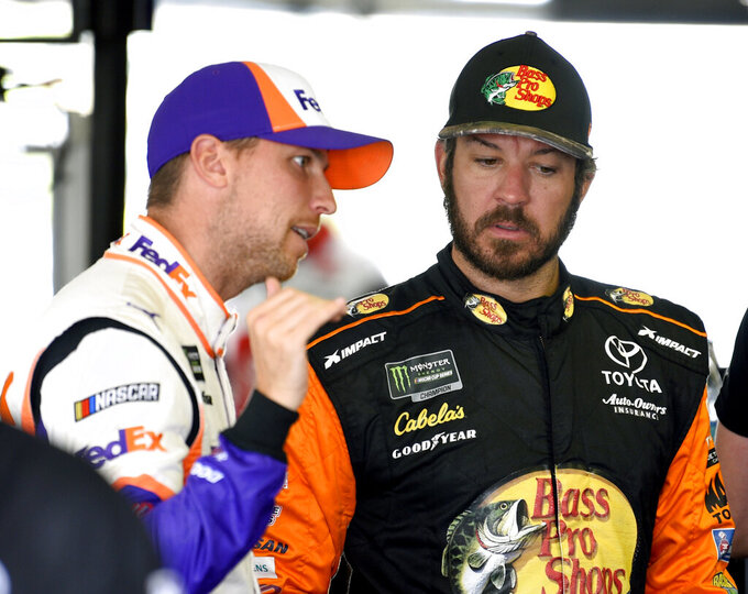 Martin Truex Jr., right, and Denny Hamlin talk in the garage area during a practice session for Sunday's NASCAR Cup Series auto race, Saturday, July 27, 2019, in Long Pond, Pa. (AP Photo/Derik Hamilton)
