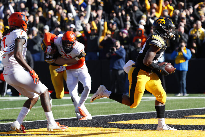 Iowa running back Tyler Goodson, right, scores on a 2-yard touchdown run ahead of Illinois defensive back Stanley Green, left, during the first half of an NCAA college football game, Saturday, Nov. 23, 2019, in Iowa City, Iowa. (AP Photo/Charlie Neibergall)