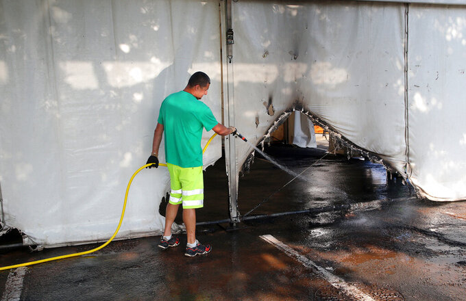 A municipality workers cleans the debris of a Covid-19 vaccination center in Urrugne, southwestern France, Monday, July 19, 2021, following an arson attack on Saturday evening. Two Covid-19 vaccination centers were ransacked in less than 48 hours in France, over the weekend. (AP Photo/Bob Edme)