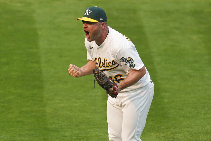 Oakland Athletics relief pitcher Liam Hendriks celebrates after striking out Chicago White Sox's Nomar Mazara for the final out of Game 3 of an American League wild-card baseball series Thursday, Oct. 1, 2020, in Oakland, Calif. The Athletics won 6-4. (AP Photo/Eric Risberg)