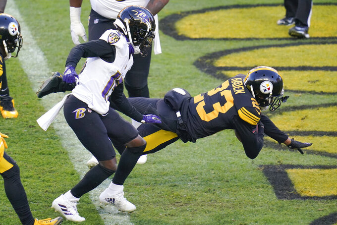 Pittsburgh Steelers cornerback Joe Haden (23) dives into the end zone with a touchdown in front of Baltimore Ravens wide receiver Marquise Brown (15) after making an interception in the first halfduring an NFL football game, Wednesday, Dec. 2, 2020, in Pittsburgh. (AP Photo/Gene J. Puskar)
