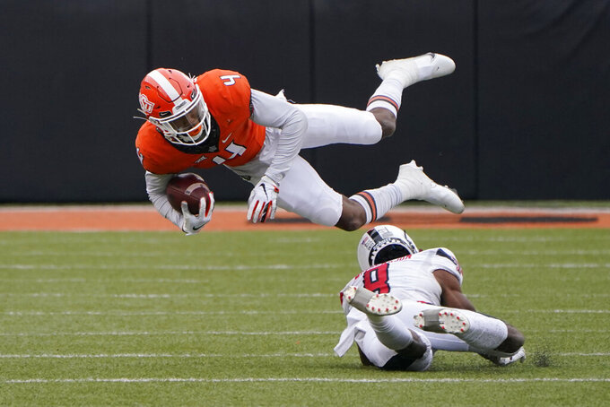 Oklahoma State wide receiver Tay Martin (4) is upended by Texas Tech defensive back Zech McPhearson (8) in the first half of an NCAA college football game in Stillwater, Okla., Saturday, Nov. 28, 2020. (AP Photo/Sue Ogrocki)