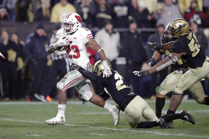 FILE - In this Saturday, Nov. 17, 2018, file photo, Wisconsin running back Jonathan Taylor (23) breaks the tackle of Purdue safety Navon Mosley (27) on his way to scoring a game-winning touchdown during overtime of an NCAA college football game in West Lafayette, Ind. The sophomore is a finalist for a second straight year for the Doak Walker Award, given to the nation's best running back. He's 131 yards short of his first 2,000-yard season as the Badgers get ready to play Minnesota this weekend in the annual rivalry game for Paul Bunyan's Axe. (AP Photo/Michael Conroy, File)