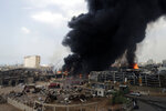 FILE - In this Sept. 10. 2020 file photo, firefighters work to extinguish a fire at warehouses at the seaport in Beirut, Lebanon. An economic meltdown, a revolution, financial collapse, a virus outbreak and a cataclysmic explosion that virtually wiped out the country's main port. The past year has been nothing short of an earthquake for tiny Lebanon, with an economic meltdown, mass protests, financial collapse, a virus outbreak and a cataclysmic explosion that virtually wiped out the country's main port. Yet Lebanese fear even darker days are ahead. (AP Photo/Hassan Ammar, File)
