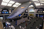 FILE - People rest in the observation area, at right, after receiving COVID-19 vaccinations under the 94-foot-long, 21,000-pound model of a blue whale, in the Milstein Family Hall of Ocean Life, at the American Museum of Natural History, in New York, Friday, April 23, 2021. After months of coaxing people to get vaccinated against COVID-19 with incentives like museum tickets and transit passes, New York City is sweetening the pot by offering $100 to any city resident who gets a first dose of a coronavirus vaccine at a city-run site, Mayor Bill de Blasio said Wednesday, July 28, 2021. (AP Photo/Richard Drew, File)