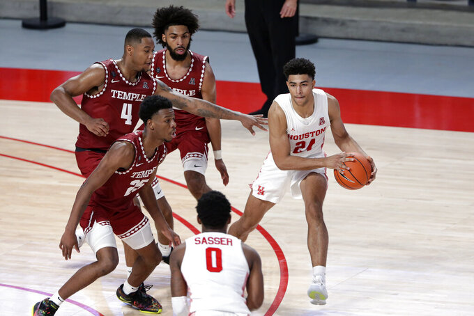 Houston guard Quentin Grimes (24) looks to pass the ball to guard Marcus Sasser (0) as Temple's Jeremiah Williams (25), J.P. Moorman II and Damian Dunn, back, defend during the second half of an NCAA college basketball game Tuesday, Dec. 22, 2020, in Houston. (AP Photo/Michael Wyke)