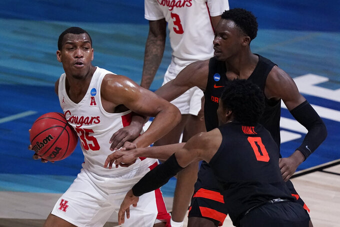 Houston forward Fabian White Jr. grabs a rebound in front of Oregon State forward Warith Alatishe, right, and guard Gianni Hunt (0) during the second half of an Elite 8 game in the NCAA men's college basketball tournament at Lucas Oil Stadium, Monday, March 29, 2021, in Indianapolis. (AP Photo/Michael Conroy)
