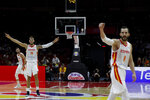 Willy Hernangomez Geuer, second from left, and Pau Ribas, right, of Spain jubilates after their teammate scored a three pointer against Serbia during their Group J second phase match for the FIBA Basketball World Cup, at the Wuhan Sports Center in Wuhan in central China's Hubei province, Sunday, Sept. 8, 2019. (AP Photo/Andy Wong)