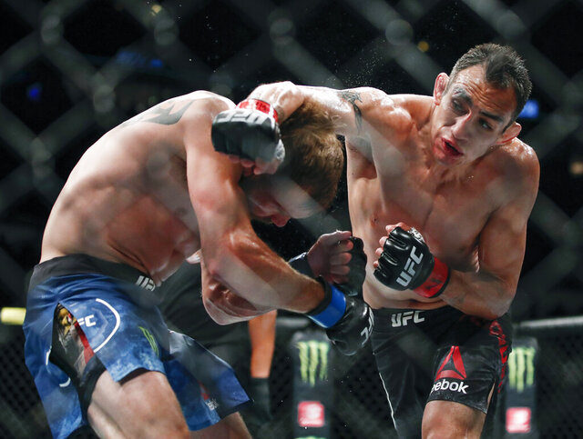 FILE - In this June 8, 2019, file photo, Tony Ferguson, right, punches Donald Cerrone, left, during their lightweight mixed martial arts bout at UFC 238 in Chicago. Ferguson and Justin Gaethje will headline the mixed martial arts card at UFC 249 behind closed doors at Veterans Memorial Arena in Jacksonville, Fla., Saturday, May 9, 2020. UFC 249 will serve as the first major sporting event to take place since the coronavirus pandemic shut down much of the country nearly two months ago. (AP Photo/Kamil Krzaczynski, File)