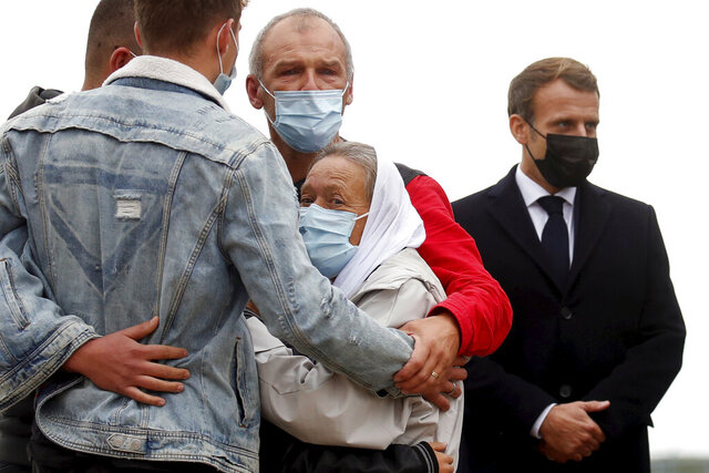 France President Emmanuel Macron, right, stands as Sophie Petronin, center, a French aid worker held hostages for four years by Islamic extremists in Mali, is greeted by relatives upon her arrival at the Villacoublay military airport near Paris, Friday Oct. 9, 2020. Sophie Petronin was released with three other hostages from Mali and Italy this week. Before leaving Mali's capital, she said she was doing well and wanted to return to Mali to resume her humanitarian work with malnourished children and orphans.(Gonzalo Fuentes, Pool Photo via AP)