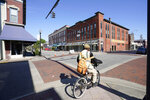 FILE - In this April 22, 2021 file photo, a man rides a bicycle downtown in Elizabeth City, N.C.  The fatal shooting of a Black man by sheriff's deputies has sent shock waves through Elizabeth City. The majority Black city in the state's rural northeastern corner holds an important place in African American history in the 19th and 20th centuries. But some residents say it seemed too close-knit and too out-of-the-way to become a flashpoint in the 21st.   (AP Photo/Gerry Broome, File)
