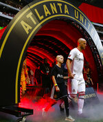 Toronto FC's Michael Bradley walks onto the field with a young fan before the team's MLS soccer match against Atlanta United in Atlanta on Wednesday, May 8, 2019. (AP Photo/Mike Zarrilli)
