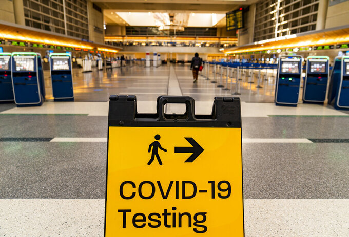 """FILE - In this Nov. 25, 2020 file photo, a COVID-19 testing sign is posted at the empty Tom Bradley International Terminal at Los Angeles International Airport.  On Friday, July 30, 2021 The Associated Press reported on stories circulating online incorrectly claiming a table shows a list of planned COVID-19 variants and when they will be """"released"""" to the public. (AP Photo/Damian Dovarganes, File)"""