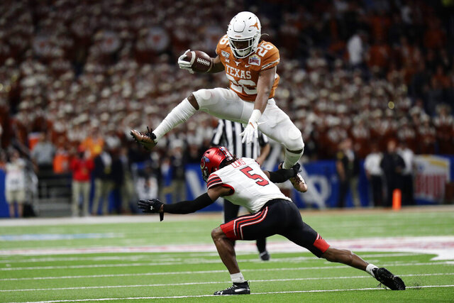 Texas running back Keaontay Ingram (26) leaps over Utah defensive back Tareke Lewis (5) during the second half of the Alamo Bowl NCAA college football game in San Antonio, Tuesday, Dec. 31, 2019. (AP Photo/Eric Gay)