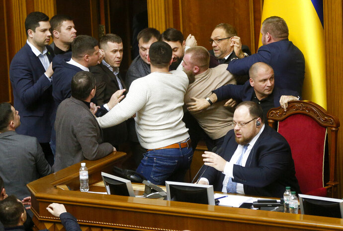 Ukrainian lawmakers scuffle around the rostrum during a parliament session in Kyiv, Ukraine, Thursday, Feb. 6, 2020. The Ukrainian parliament to considering the law to lift the ban on sales of farmland. (AP Photo/Efrem Lukatsky)