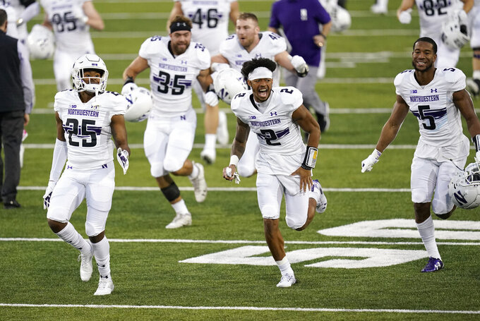 Northwestern players run off the field after an NCAA college football game against Iowa, Saturday, Oct. 31, 2020, in Iowa City, Iowa. Northwestern won 21-20. (AP Photo/Charlie Neibergall)