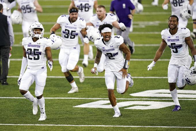 Northwestern players run off the field after an NCAA college football game against Iowa, Saturday, Oct. 31, 2020, in Iowa City, Iowa. Northwestern won 21-20. (AP Photo/Charlie Neibergall)