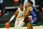 Duke forward Wendell Moore Jr. (0) defends Miami forward Anthony Walker (1) during the first half of an NCAA college basketball game, Monday, Feb. 1, 2021, in Coral Gables, Fla. (AP Photo/Marta Lavandier)