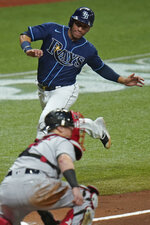 Tampa Bay Rays' Michael Perez begins to slide around Boston Red Sox catcher Christian Vazquez to score on a two-run double by Austin Meadows off pitcher Matt Hall during the fourth inning of a baseball game Friday, Sept. 11, 2020, in St. Petersburg, Fla. (AP Photo/Chris O'Meara)