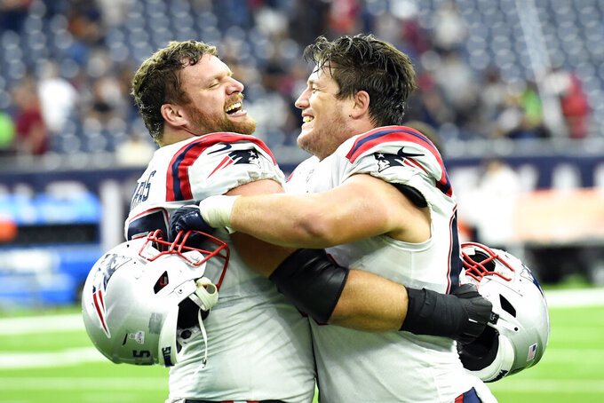 New England Patriots' Ted Karras, left, and James Ferentz celebrate after an NFL football game against the Houston Texans Sunday, Oct. 10, 2021, in Houston. (AP Photo/Justin Rex)