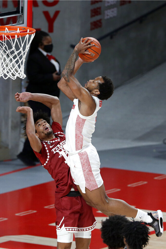 Houston forward Justin Gorham, right, puts up a shot over Temple forward Jake Forrester, left, during the second half of an NCAA college basketball game Tuesday, Dec. 22, 2020, in Houston. (AP Photo/Michael Wyke)