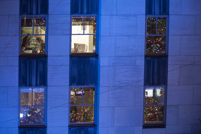 FILE - In this Nov. 28, 2018, file photo people work in their office after the Rockefeller Center Christmas tree is lit during the 86th annual Rockefeller Center Christmas tree lighting ceremony in New York. Holiday staffing is one of a small business owner's biggest stressors. Even companies that aren't retailers or restaurants can have a year-end busy season, just when employees all want to take time off. (AP Photo/Mary Altaffer, File)