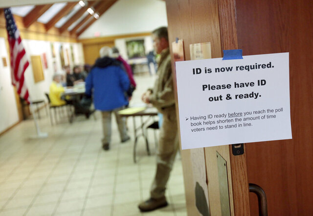 FILE - In this Feb. 16, 2016, file photo, a sign informs voters of the need for identification at the Olbrich Gardens polling location in Madison, Wis. Democrats are hoping this is the year they can finally make political headway in Texas and have set their sights on trying to win a majority in one house of the state legislature. Among the big hurdles they'll have to overcome are a series of voting restrictions Texas Republicans have implemented in recent years, including the nation's toughest voter ID law, purging of voter rolls and reductions in polling places. (Michael P. King/Wisconsin State Journal via AP, File)