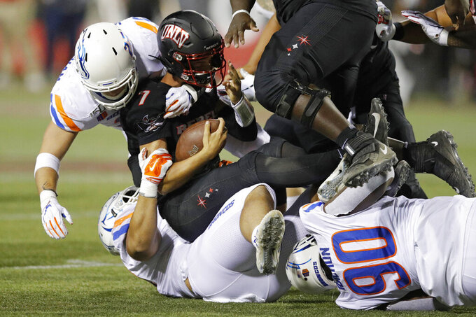 From left, Boise State Broncos' Benton Wickersham, Sonatane Lui and Scale Igiehon (90) tackle UNLV quarterback Kenyon Oblad during the first half of an NCAA college football game Saturday, Oct. 5, 2019, in Las Vegas. (AP Photo/John Locher)